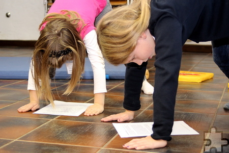 Mit dem Kopf im Vierfüßler-Stand nach unten auf die Erde blickend lesen, das konnten die Kinder bei einem Workshop der Lerntherapeutin  Meike Jürgensen. Foto: Kirsten Röder /pp/Agentur ProfiPress