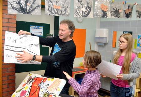 Mit den Kindern bespricht Künstler Stephan Schick die Arbeiten. Die schönsten Bilder kommen für die Ausstellung beim Schulfest in eine Sammelmappe. Foto: Renate Hotse/pp/Agentur ProfiPress