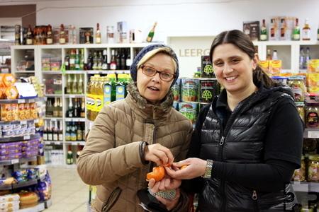 """""""Hier darf noch probiert werden, bevor man das Obst kauft"""", sagt Aynur Karacan und schält ihrer Kundin eine Mandarine. Foto: Alice Gempfer/pp/Agentur ProfiPress"""