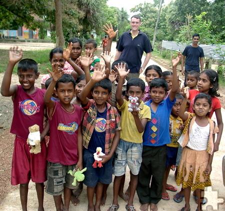 Thomas Schwarzer (l.) mit einer Gruppe von Kindern, die sich über die mitgebrachten Spielsachen freute. Im Hintergrund Vertrauensmann Ranchan, ein ehemaliger Priester der methodistischen Kirche. Foto: Privat/pp/Agentur ProfiPress