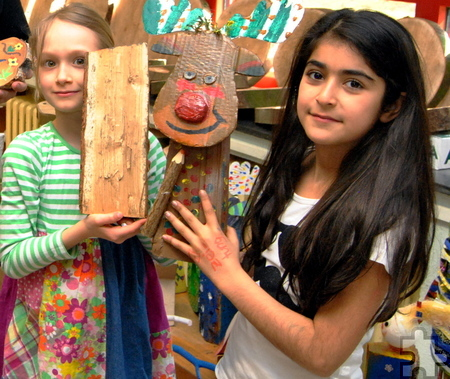 Leona (l.) hält einen unbehandelten Holzklotz in ihren Händen, während Havin zeigt, was in der Kunst-AG mit Stephan Schick daraus entstanden ist. Foto: Renate Hotse/pp/Agentur ProfiPress