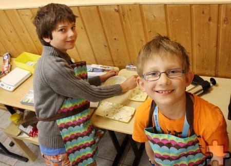 Simon (links) und Sebastian sind fleißig: Aus Schokolade stellen sie Pralinen her, die später im Supermarkt verkauft werden. Foto: Steffi Tucholke/pp/Agentur ProfiPress