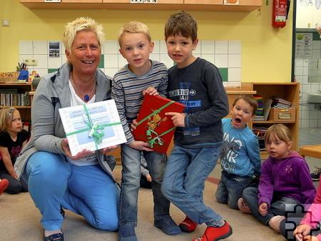 """Beatrix Fröhlich vom Verein """"Jugendzahnpflege des Kreises Euskirchen e.V."""" überreichte den Kindern eine Urkunde sowie ein Bild vom """"Goldenen Jimmy"""". Foto: Privat/pp/Agentur ProfiPress"""