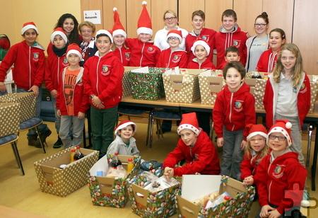 Mit ihren roten Mützen könnten sie auch Weihnachtselfen sein: Die Kinder des Jugendrotkreuzes haben sich stolz um ihre Weihnachtspakete für die Mechernicher Tafel versammelt. Foto: Steffi Tucholke/pp/Agentur ProfiPress