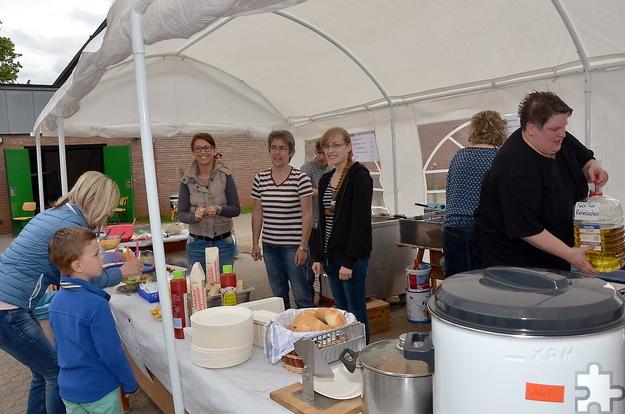 Für Eltern, Geschwister und Großeltern der Lückerather Grundschulkinder gab es am Sonntag beim Schulfest eine Menge Betätigungsmöglichkeiten – beispielsweise, wie hier, im Küchenzelt bei der Herstellung von Fritten, Schnibbelfleisch und Reibekuchen. Es gab auch eine Cafeteria mit selbstgebackenen Kuchen. Foto: Manfred Lang/pp/Agentur ProfiPress
