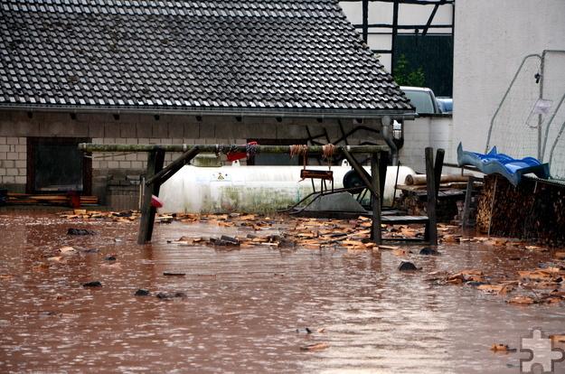 Brennholz als Treibholz in den Wasserfluten, im Hintergrund ein Flüssiggastank. Foto: Thomas Schmitz/pp/Agentur ProfiPress