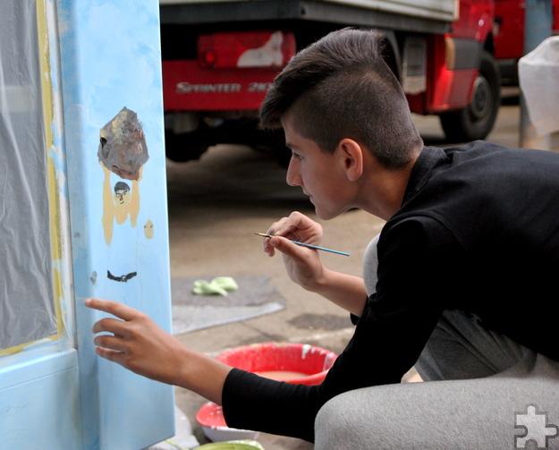 Auch zwei Flüchtlingskinder waren unter den Kindern der Offenen Jugendarbeit Titz. Eines von ihnen verewigt die Sage vom Mann, der einen Felsen trägt, aus seiner Heimat Albanien auf der von Maf Räderscheidt gestalteten Telefonzelle. Foto: Thomas Schmitz/pp/Agentur ProfiPress