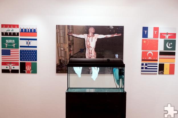 """Die Journalistin Jana Assauer schreibt über diese Installation von Hermann J. Kassel: """"Diese zentrale Mixed-Media-Installation stellt bearbeitete Fotografien von George Bush und dem Foltergefängnis Abu Ghraib einem Aquarium gegenüber, in dem sich zwei weiße Handschuhe unablässig bewegen, sich berühren, umeinanderkreisen."""" """"Symbole für all' die Hände, die in Unschuld gewaschen werden"""", erklärt Hermann J. Kassel. Der gefolterte Mann aus Abu Ghraib ist für ihn zum Sinnbild dafür geworden, """"was Menschen Menschen antun. Ein Mensch, dem seine Würde mit brutaler Deutlichkeit genommen wurde."""" Foto: Jana Assauer/pp/Agentur ProfiPress"""
