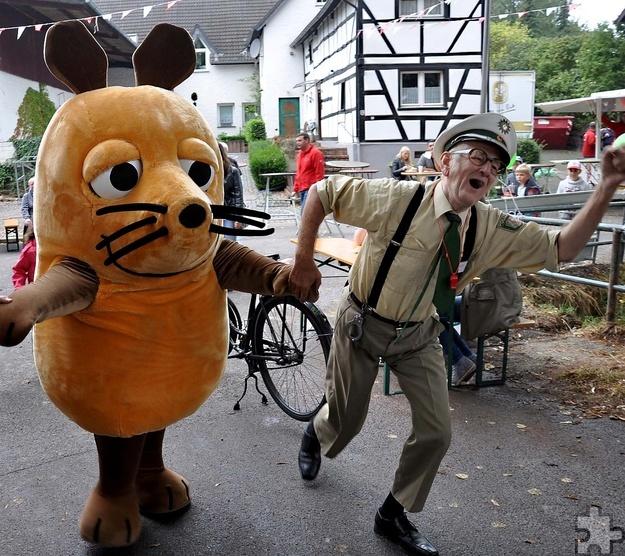 """Auch Schutzmann """"Zwille"""" Zimmermann war auf dem Lückerather Rummelplatz zu Gast und nahm die WDR-Maus an die Hand, um sie zur Bühne zu begleiten. Foto: Reiner Züll/pp/Agentur ProfipressMaus:"""