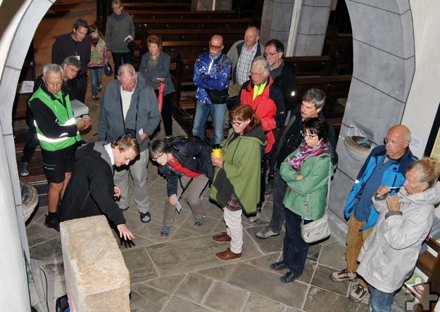LVR-Mitarbeiter Eugen Rung (l.) erklärt den Besuchern in der Weyerer Pfarrkirche die Inschrift des Matronensteins. Foto: Renate Hotse/pp/Agentur ProfiPress