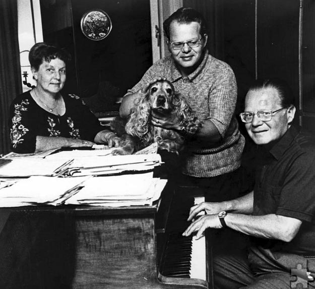 """Anni, Helmut und Toni Steingass 1979 mit ihrem Hund """"Hobby"""" in ihrem Haus in Kommern. Am Flügel im Wohnzimmer entstanden viele bekannte Stimmungslieder. Foto: Reiner Züll/pp/Agentur Profipress"""