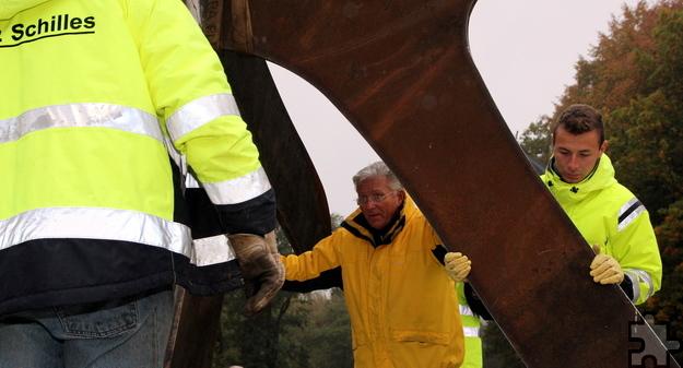 """Der Künstler Günter Preuss aus Schützendorf legt bei der Platzierung seines Kunstwerks """"Zeitzeichen"""" Hand an. Foto: Thomas Schmitz/pp/Agentur ProfiPress"""