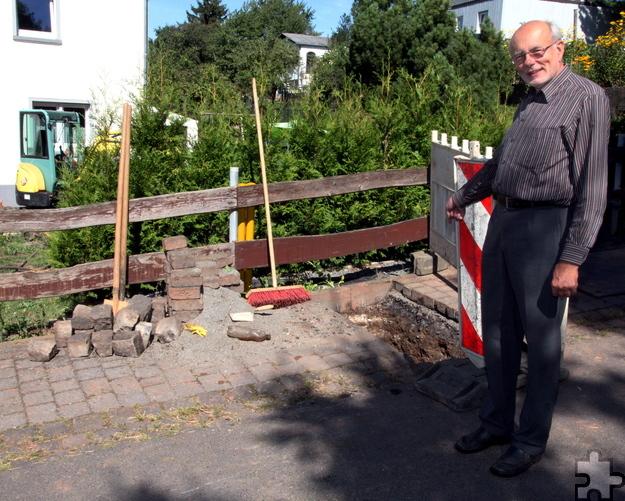 In dieses Haus an der Schmiedegasse unweit der Bahngleise war ein schwerer Wasserschaden entstanden. Ortsvorsteher Hans Reiff zeigt, wo Kanalarbeiten stattfinden. Foto: Thomas Schmitz/pp/Agentur ProfiPress