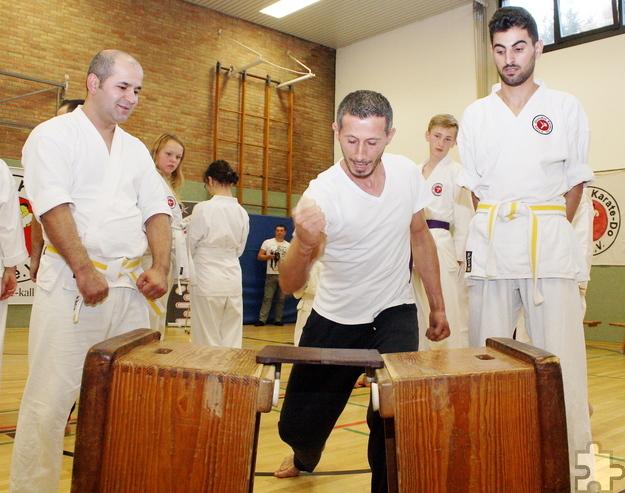 Eduart Murrani (Mitte) versucht im Karate-Training ein spezielles Bruchtestbrett zu zerschlagen. Makhmadrajab Saidaliev (links) und Ahmad Ahzyab (rechts) unterstützen ihn dabei. Foto: Steffi Tucholke/pp/Agentur ProfiPress