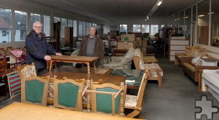 In den ehemaligen Räumlichkeiten von Dörries Scharmann in Vussem ist ein riesiges Möbellager untergebracht, das Helmut Vogelsberg (l.) und Rainer Gottschlich zeigen. Foto: Thomas Schmitz/pp/Agentur ProfiPress