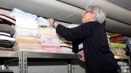 Christel Warmer räumt und sortiert Kleidungsstücke unter der Decke des ehemaligen Werkraums der St.-Barbara-Schule. Foto: Thomas Schmitz/pp/Agentur ProfiPress