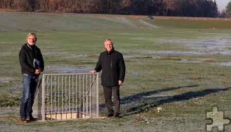 Jörg Nußbaum (l.) und Helmut Schmitz stehen neben dem dreidimensionalen Abfluss inmitten des Hochwasserrückhaltebeckens bei Antweiler. Foto: Thomas Schmitz/pp/Agentur ProfiPress