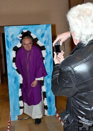 Künstler Franz Kruse fotografiert Pfarrer Erik Pühringer beim Durchgang durch seine Schemenwand von draußen in die Kirche hinein. Foto: Manfred Lang//pp/Agentur ProfiPress