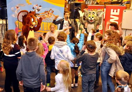 Alle Hände hoch: Kinderliedersänger Uwe Reetz (rechts) mit Schlafhaube im Rewe-Center. Foto: Reiner Züll/pp/Agentur ProfiPress