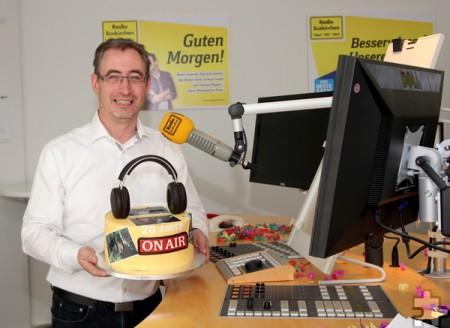 Radio-Euskirchen-Chefredakteur Norbert Jeub ist seit 20 Jahren im Dienst – und freute sich über die gigantische, mit einem größtenteils essbaren Kopfhörer verzierte Torte. Foto: Thomas Schmitz/pp/Agentur Profipress