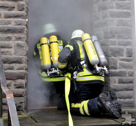 Vorsichtig, auf den Knien kriechend, dringen die ersten Wehrleute in das verrauchte Haus ein. Foto: Reiner Züll/pp/Agentur ProfiPress