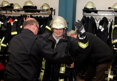 Weil Sandra Lüttgen wissen wollte, wie schwer eine Feuerwehruniform ist, kleidete Kalls Löschzugführer Thomas Golüke die SPD-Kassiererin kurzerhand ein. Foto: Thomas Schmitz/pp/Agentur ProfiPress