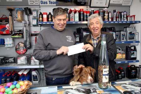 Christian Meurer (l.) überreichte Willi Greuel 1950 Euro für die Hilfsgruppe Eifel. Meurers Hund Sunny hat derweil die neue Spendenflasche im Blick. Foto: Thomas Schmitz/pp/Agentur ProfiPress