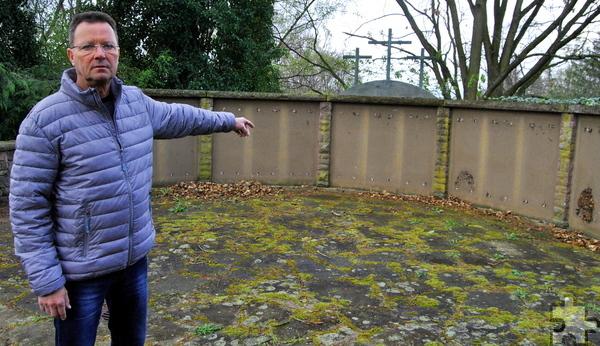 Dieter Cuber, bei der Stadt Mechernich zuständig für Friedhofsangelegenheiten, zeigt auf die kahlen Mauern des Ehrenmals. Alle 15 Bronzeplatten wurden gestohlen. Foto: Renate Hotse/pp/Agentur ProfiPress