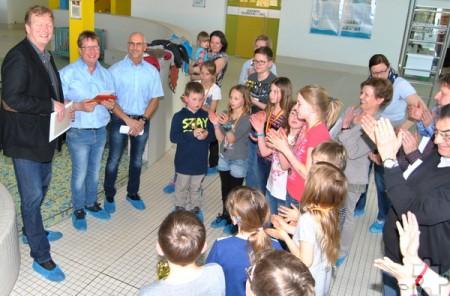 Mit einem kleinen Präsent und kräftigem Applaus bedankten sich die Schulleiter und Grundschüler der Mechernicher Grundschulen bei Peter Jansen (2.v.l.) und Frank Dudzinski (3.v.l.) von der DLRG-Ortsgruppe Mechernich für die Aufsicht und Unterstützung beim Sponsorenschwimmen. Foto: Renate Hotse/pp/Agentur ProfiPress