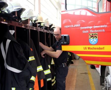 Bei geöffneter Fahrzeugtür birgt das Umziehen am Spind ein hohes Verletzungsrisiko, wie Jörg Opielka demonstriert. Schon allein deshalb braucht die Feuerwehr mehr Platz. Foto: Thomas Schmitz